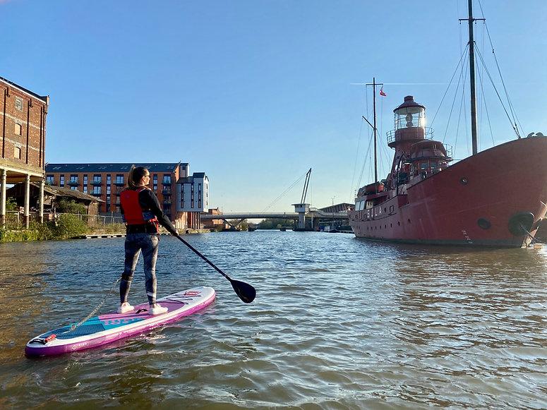 Lady Paddleboarding SUP lighthouse boat