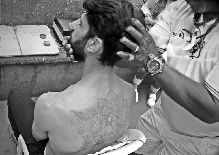 """Walter González, más conocido como """"barquito"""", aplica sus conocimientos de sobador con uno de los integrantes de Libre Razón. Sus manos curadoras y expertas forman parte del paisaje informal de Santo Domingo."""