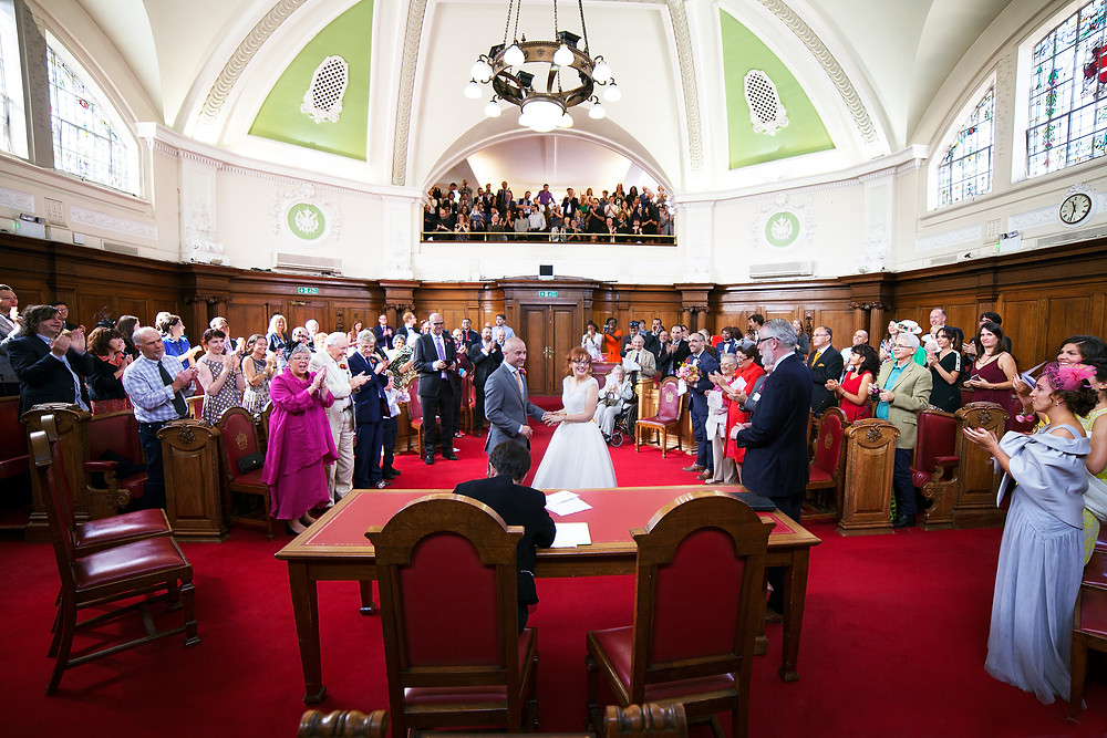 Guests (including Artman English members) applauding the end of Oli and Paloma's London wedding ceremony at Islington Town Hall (Council Chamber)
