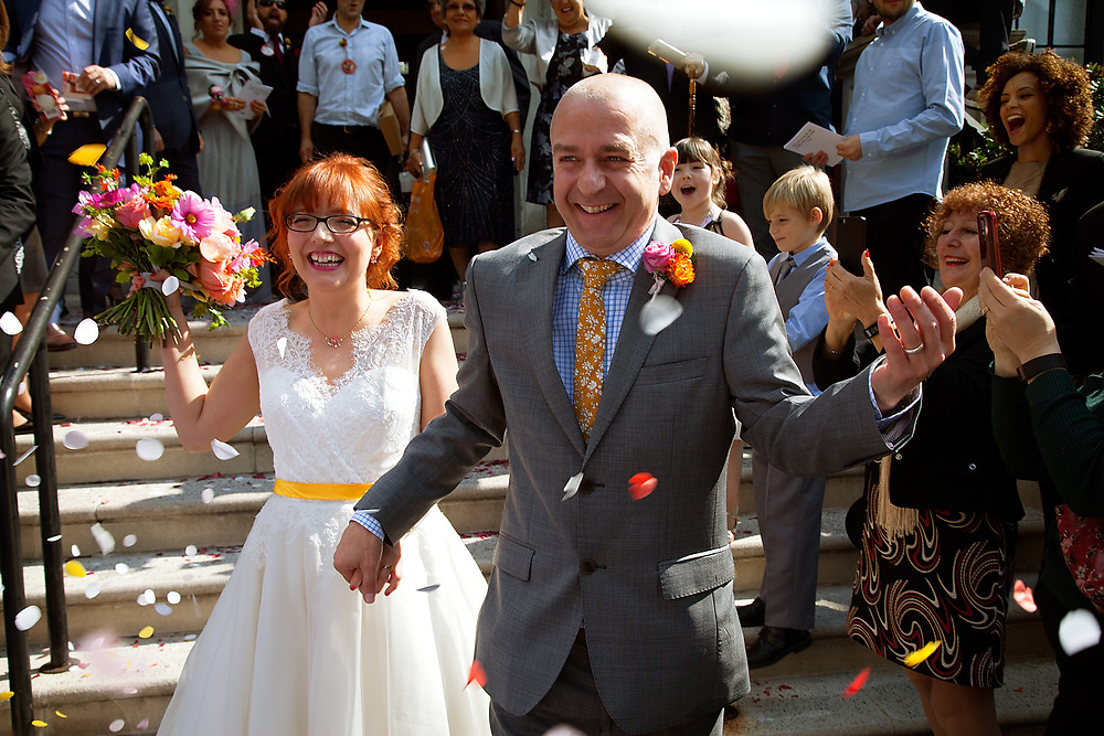 Mr (Oli) & Mrs (Paloma) walk down Islington Town Hall steps under a rain of confetti