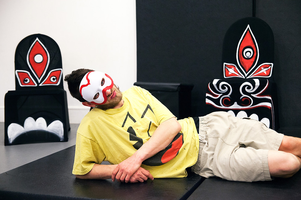 Carlos Cashiero, set designer of Queen Lear (Artman English adaptation of King Lear), wearing a theatre mask and reclined amongst his work in progress
