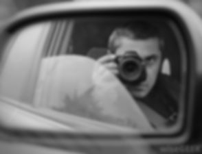 man-in-black-and-white-taking-photos-in-car.jpg