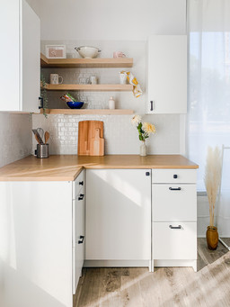 Small kitchen corner with white cabinets.