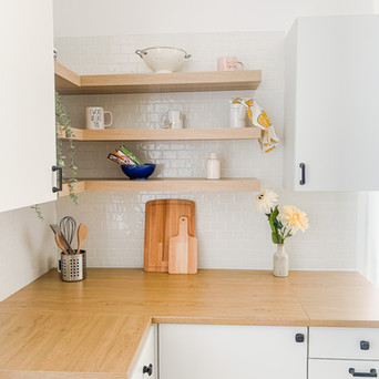 Close up of a kitchen corner. There is white subway tile on the wall and 3 floating shelves.