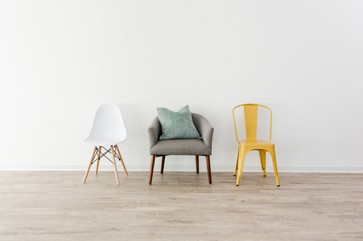 3 chairs. One white midcentury modern chair, a gray armchair, and a yellow metal chair.