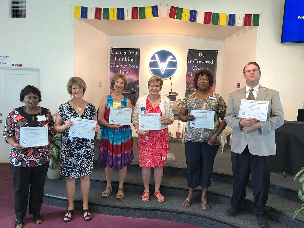 a group of people holding certificates
