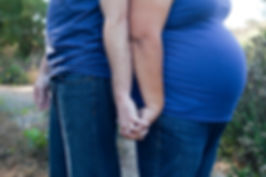 Pregnant mother holding supportive partner, father, dad's hand.