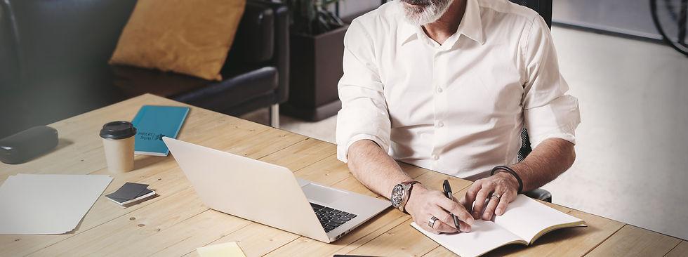Service von Notizgold: Ein Geschäftsmann schreibt Notizen in sein qualitativ hochwertiges Notizbuch von Notizgold mit Logo lasergraviert.