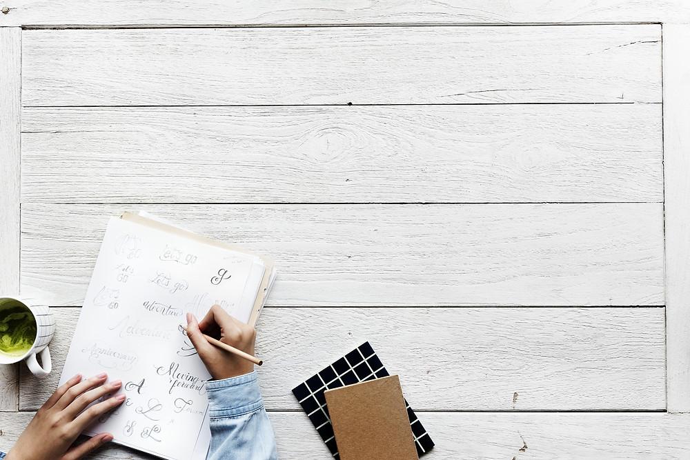Frau schreibt in Ihr Notizbuch - Notizgold berät Sie gerne, wenn Sie auf der Suche nach Ihrem individualisierten und personalisierten Unternehmensnotizbuch sind