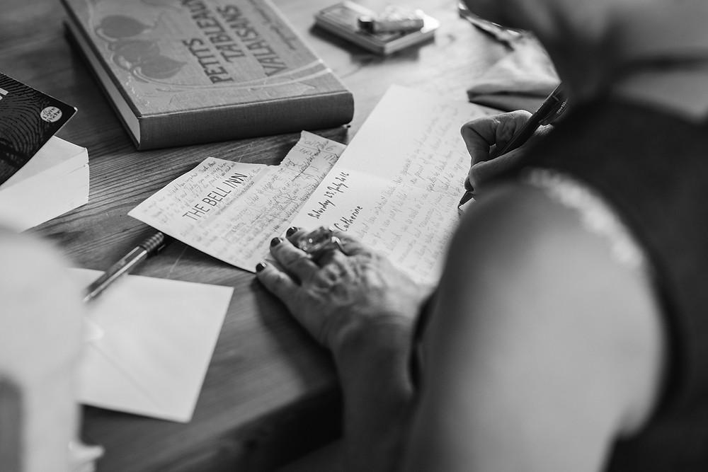 Frau schreibt in ihr Notizbuch - Entschleunigung mit Notizgold