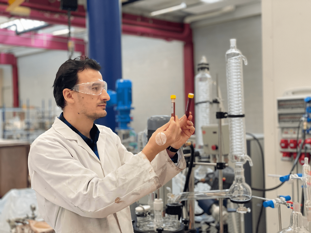 Adnan Akcay, bioprocess engineer in Kaffe Bueno, holds two test tubes