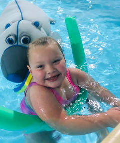 girl in a pool with a polar bear float