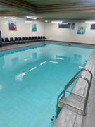 swimming pool and chairs with pool ladde