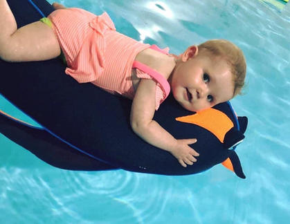 baby lying on a penguin float