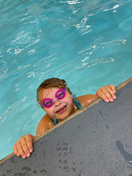 child at the side of a swimming pool