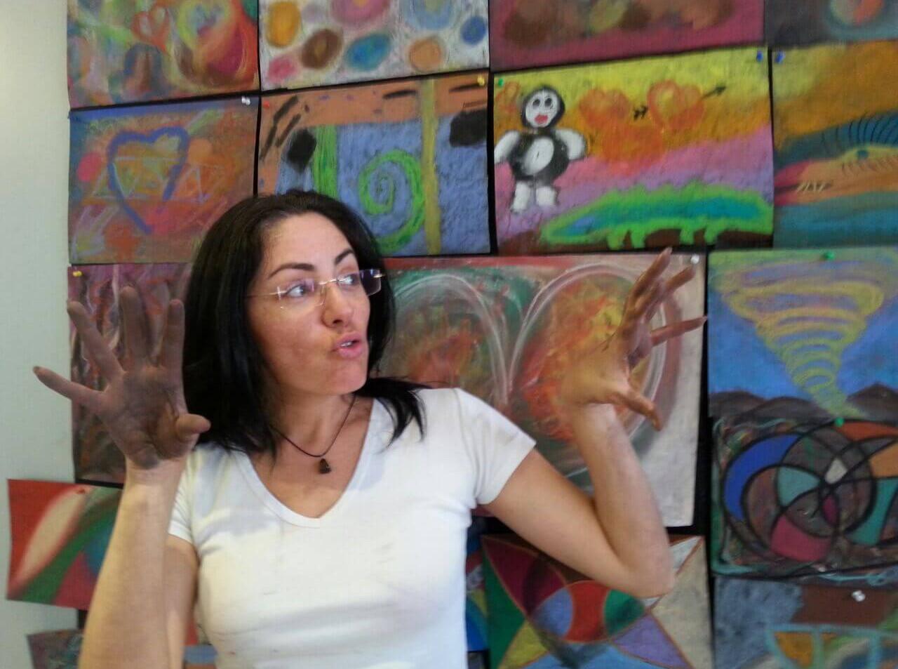 מציירת על רקע תערוכת ציורים אינטואיטיביים