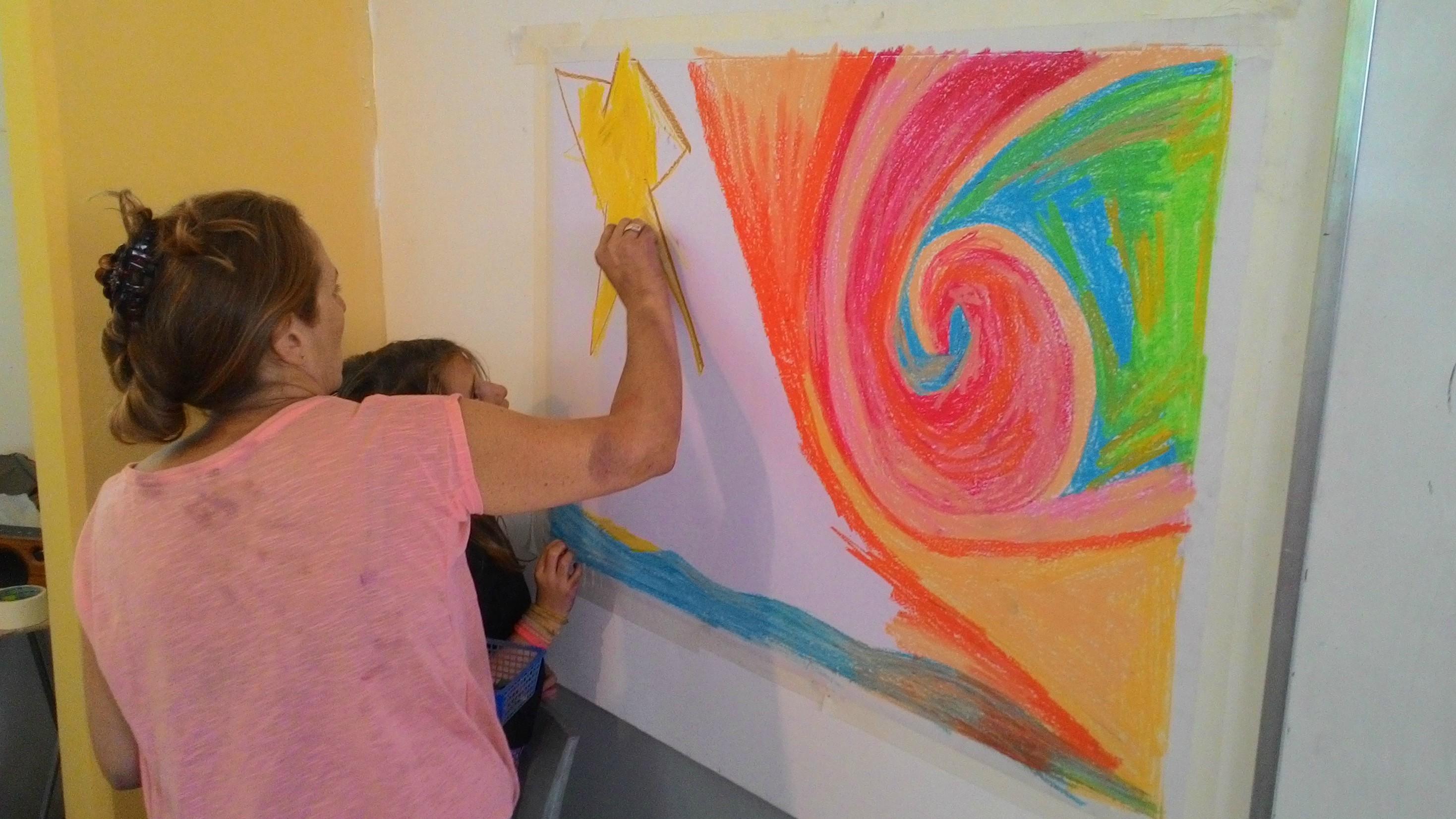 אמא ובת מציירות בצבעי םנדה על הקיר
