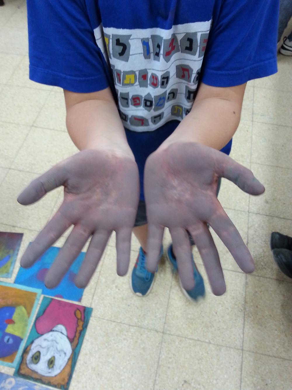 ידיים של ילד על רקע ציור אינטואיטיבי