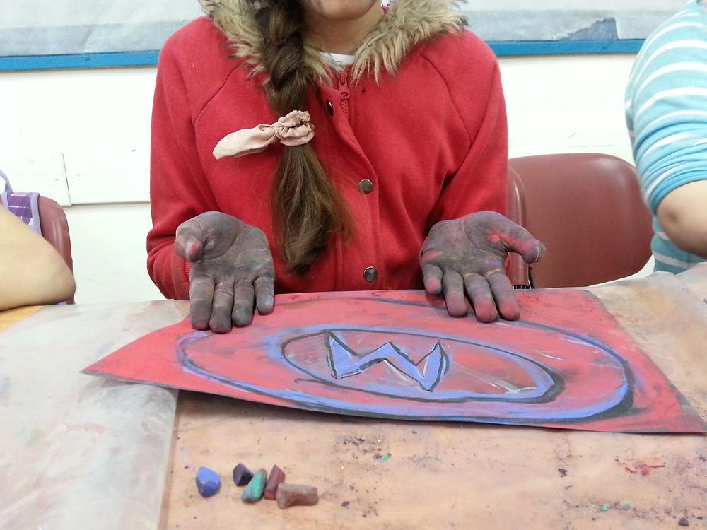 ילדה בסדנא מציגה ציור אינטואיטיבי באדום וכחול