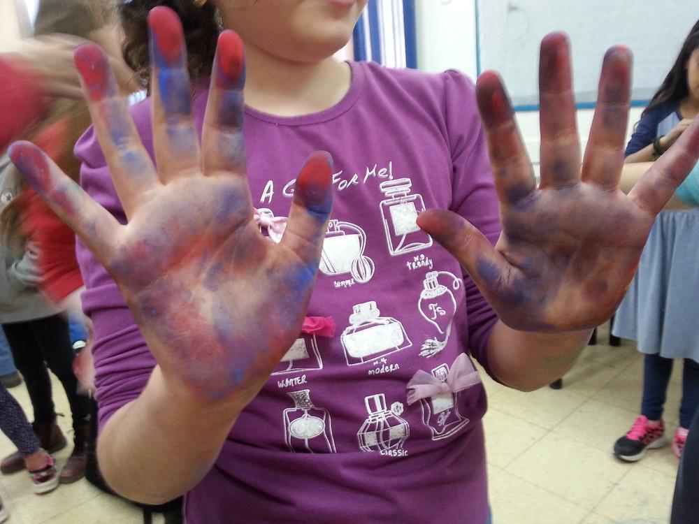 ילדה בסדנאת ציור אינטואיטיבי, עם ידיים בכחול וסגול
