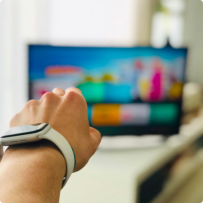A hand wearing an Apple Watch pointing at a TV, using the Magicho app to control it.