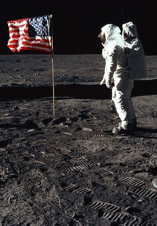Astronauta saludando junto a bandera USA en la Luna