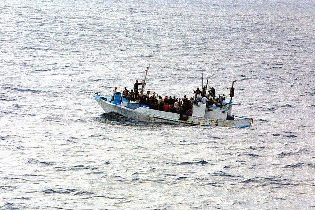 Letras HELP e imágenes de embarcación con migrantes alrededor