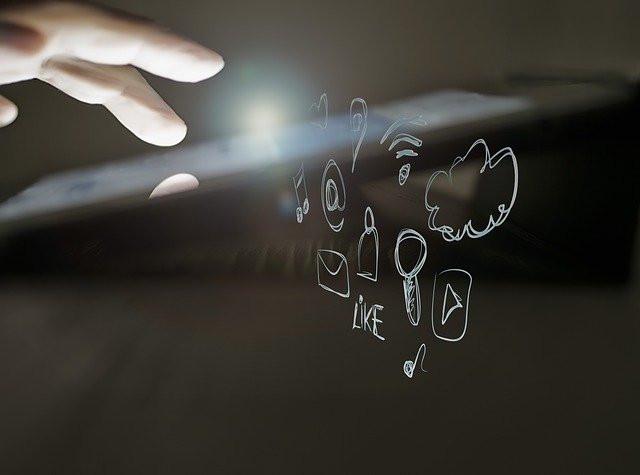 Pantalla táctil en que una mano teclea y se ven caracteres idealizados propios de las redes sociales