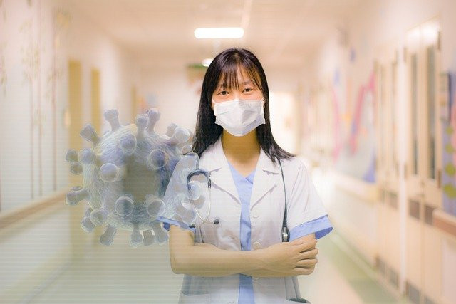 Enfermera oriental en pasillo de Hospital con una partícula del coronavirus difuminada