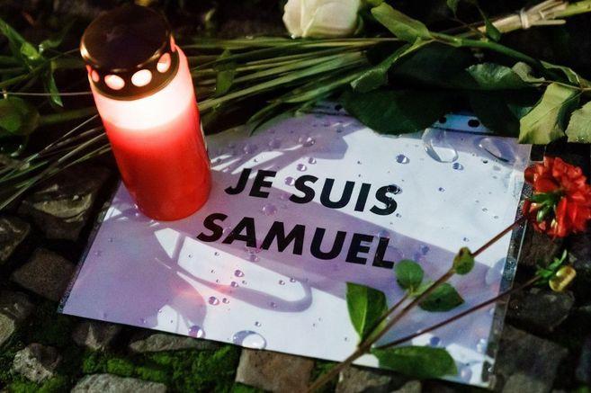 Vela encendida junto a un papel que dice: Je suis Samuel