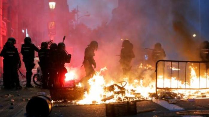 Manifestantes encapuchados detrás de barricada incendiada