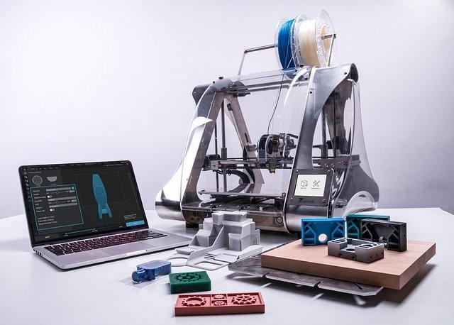 Mesa con impresora 3D, portátil y varios artículos