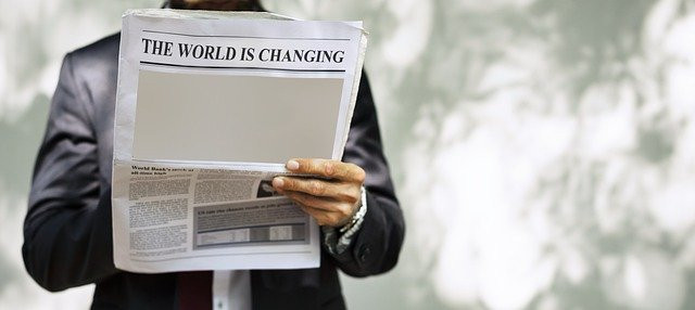 """Hombre leyendo periódico donde se lee """"The World is changing"""""""