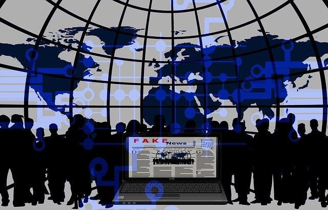 Portátil con fake news y de fondo muchas personas con un mapa mundi detrás