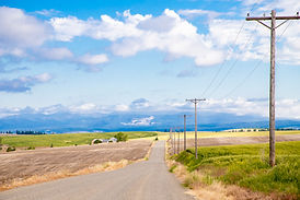 Image of gravel road and power lines and pole on right side. Mountains in distance