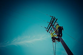 Image of two utility workers on power pole