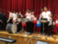 Drumline and Band students on stage
