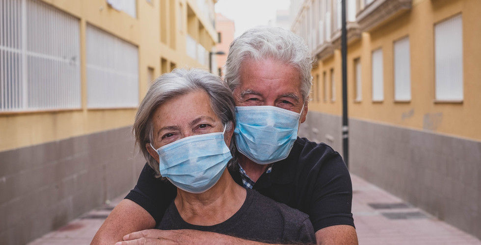 couple of two seniors wearing medical ma