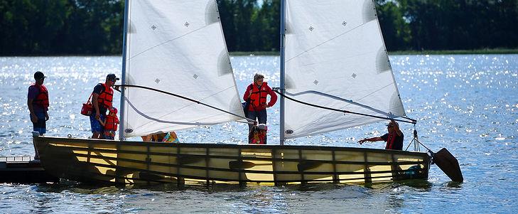 bateau à voile sur l'eau avec 6 personnes à son bord