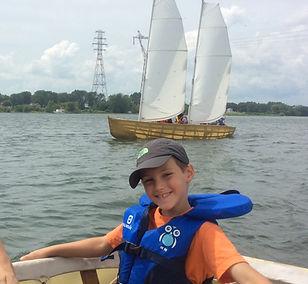 enfant qui sourit sur un bateau à voile sur l'eau