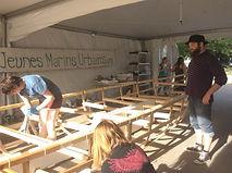 Des adultes travaillent ensemble à la construction d'un bateau à voile