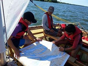 trois personnes sur un bateau à voile qui regardent une carte