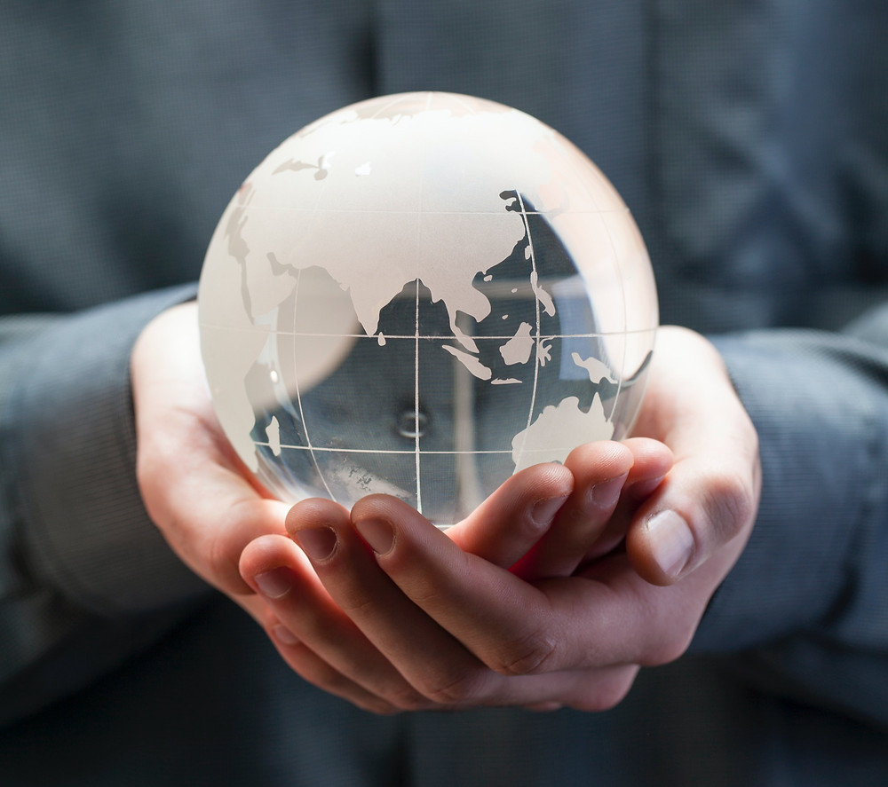 An adult holding a globe