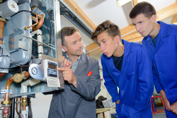 Man looking at digital display on boiler with two apprentices