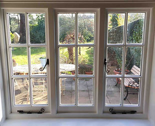 Wooden casement window looking out onto a patio, installed and fitted by Forster Timber Windows