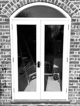 A newly installed and bespoke set of timber patio doors and a wooden arch, made by Forster Timber Windows