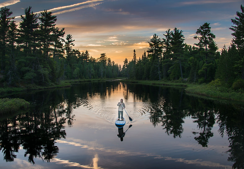 Person paddle boarding on water at sunset
