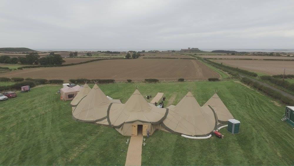 tipis - venue bamburgh castle in backgro