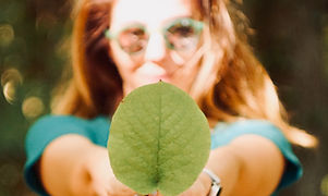 Mulher segurando folha de árvore para a câmera