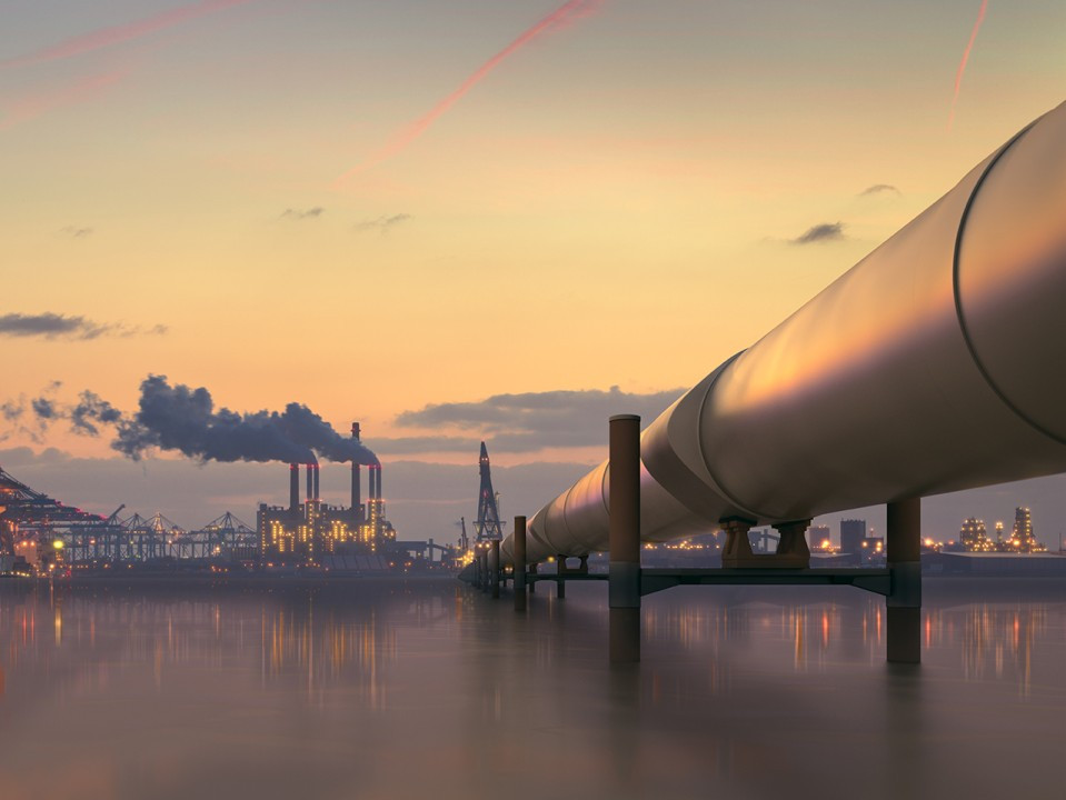 Industrial sector with pipe over a body of water